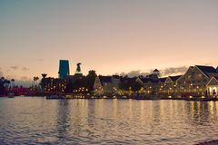 Taxi boat, colorful hotel and iluminated villas on sunset background, at Lake Buena Vista. stock photography