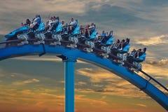 People enjoing amazing Mako roller coaster at Seaworld on beatiful sunset sky background. royalty free stock images