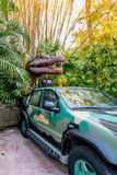 ORLANDO, FLORIDA, USA - DECEMBER, 2017: Dinosaur between the bushes with his mouth open showing his teeth over a car in theme park stock image