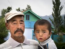 Man with child on arm, in old village stock image