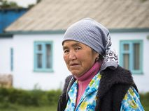 Old woman with head-bow in front of a house stock photography