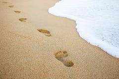 Orme nell'onda del mare e della sabbia Fotografie Stock Libere da Diritti