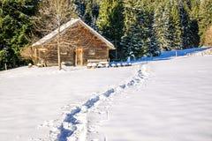 Orme in neve che conduce alla vecchie cabina e foresta di legno Allgau, Baviera, Germania, alpi Immagini Stock