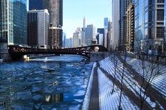 Orme sui punti innevati che conducono giù ad un Chicago River congelato a gennaio immagine stock libera da diritti