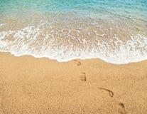 Orme sull'acqua di mare del turchese e della sabbia fotografie stock