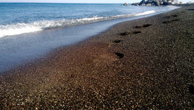 Orme sulla riva di mare sulla sabbia nera Onda del mare nei precedenti Fotografie Stock