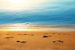 Orme sulla sabbia lungo il mare all'alba Fotografia Stock Libera da Diritti
