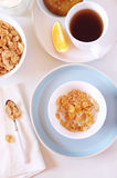 Сorn flakes in bowl,  milk and cup of tea Stock Photo