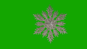 Ornament in the form of a snowflake on a green stock video footage