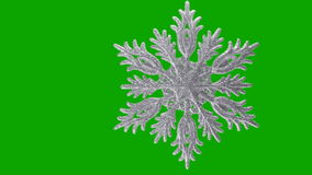 Ornament in the form of a snowflake on a green stock video