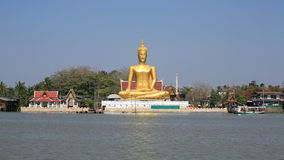 Ornament: huge gold buddha statue near river Royalty Free Stock Image