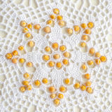 Ornament peas laid out on the crocheted tablecloth Stock Images