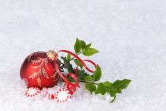 Ornament on snow with peperment candy and holly Royalty Free Stock Photo