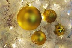 Ornament van de Kerstmis het gouden bal op kunstmatige witte pijnboomboom Stock Foto's