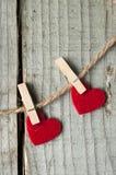 Ornament voor de Dag van Valentine Twee die harten van rood worden gemaakt op wasknijpers/wasknijper wordt gevoeld Royalty-vrije Stock Foto