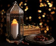 Ornamental Arabic lantern with burning candle glowing at night and glittering golden bokeh lights. Festive greeting card royalty free stock photo