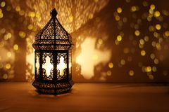 Ornamental Arabic lantern with burning candle glowing at night and glittering golden bokeh lights. Festive greeting card. Invitation for Muslim holy month royalty free stock images