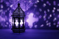 Ornamental Arabic lantern with burning candle glowing at night and glittering stars shaped bokeh lights. Festive. Greeting card, invitation for Muslim holy royalty free stock photos
