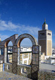 Ornamental arches on roof top terrace and mosque tower in Tunisia Royalty Free Stock Photos