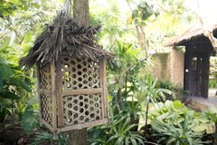 Ornamental Bamboo Lamp Post or Bird Cage. Ornamental bamboo lamp post on balinese garden. Empty wooden bird cage hanging on the tree stock images