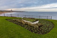 Ornamental Boat containing Flowers, with Tynemouth`s Coastline i. Winter scene of Ornamental Boat containing Flowers, with Tynemouth`s Coastline in the Stock Photo