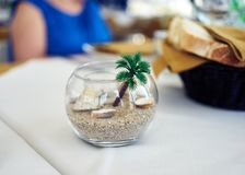 Ornamental bowl on a restaurant table. Close-up view of a glass bowl with sand Royalty Free Stock Photo