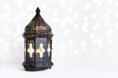 Ornamental dark Moroccan, Arabic lantern on the white table. Burning candle, glittering bokeh lights stars. Greeting. Card for Muslim community holy month Royalty Free Stock Image