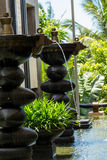 Ornamental fountain. In a shallow pond in a landscaped garden outside a building or house in Bali with jets of water cascading into the pool below and lush Royalty Free Stock Photography
