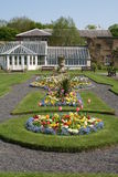 Ornamental Garden and Victorian Greenhouse. An ornamental garden with a Victorian Greenhouse in the background stock images