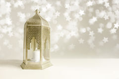 Ornamental golden Arabic lantern on the table with glittering star-shaped bokeh lights. Greeting card for Muslim Royalty Free Stock Photos