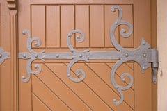Ornamental Iron Hinge On An Old Wooden Door Stock Photo