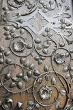 Ornamental ironwork. On brown wooden door royalty free stock photo