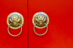 Ornamental knockers on red door Stock Image