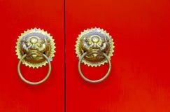 Ornamental knockers on red door Stock Image