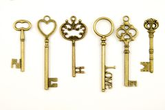 Ornamental medieval vintage keys with intricate forging, composed of fleur-de-lis elements, victorian leaf scrolls and heart shape Royalty Free Stock Photo