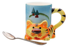 Ornamental mug tiger with spoon. Ornamental mug tiger with old cupronickel spoon Stock Images