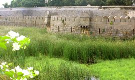 Ornamental old stone wall of vellore fort with grass field. A ruined fort battlement with grass field at Vellore fort is a large 16th-century fort situated in Stock Photo