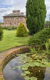 Ornamental pond in country estate. An ornamental pond in a country estate garden with a large house in the background Royalty Free Stock Image