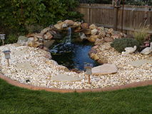 Ornamental pond in garden. Scenic view of ornamental pond with waterfall in garden surrounded by stones and rockery Royalty Free Stock Photography