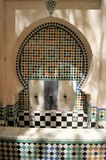 Ornamental public water dispensor enwrapped in shadows sits in the old Medina of Fez, Morocco Stock Images