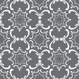 Ornamental seamless pattern. Vintage template. Curve white elements. On the gray background. Filigree texture Stock Photos