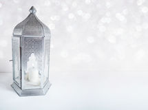 Ornamental silver Arabic lantern on the table with glittering bokeh lights. Greeting card for Muslim community holy Stock Photo