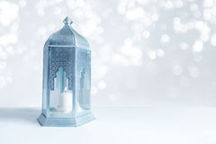Ornamental silver and blue Arabic lantern on the table with glittering bokeh lights. Greeting card for Muslim community Royalty Free Stock Image