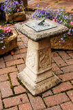 Ornamental sundial statue. Ornamental sundial in a small paved garden Royalty Free Stock Photos