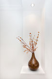 Ornamental vase with artificial  stick branches and leaves in it. Shiny vase is probably made by pasting small wooden parts together shaping as a bottle gourd Stock Photo