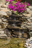 Ornamental waterfall with flowers. Fragment. Ornamental waterfall with flowers. landscape design stock image