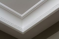 Ornamental white molding decor on ceiling of white room close-up detail. Interior renovation and construction concept. Ornamental white molding decor on ceiling royalty free stock photos