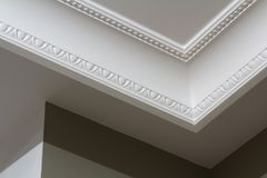 Ornamental white molding decor on ceiling of white room close-up detail. Interior renovation and construction concept. stock photos