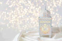 Ornamental white Moroccan, Arabic lantern on silk textile throw. Burning candle, glittering bokeh lights. Greeting card. For Muslim community holy month Ramadan royalty free stock images