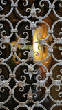Ornamental window guard with bars. Photo closeup of ornamental window guard with aged white rusty metal burglar bars on blurred glassy background, vertical royalty free stock photo